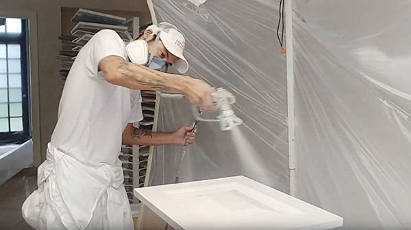 Pro painter spraying a cabinet door for kitchen painting project, Alamo Heights